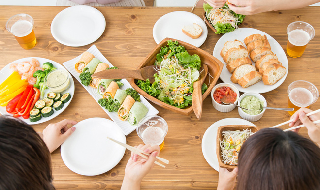 top view of group of people having dinner together at wooden table