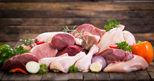 Different types of raw meat on a wooden table